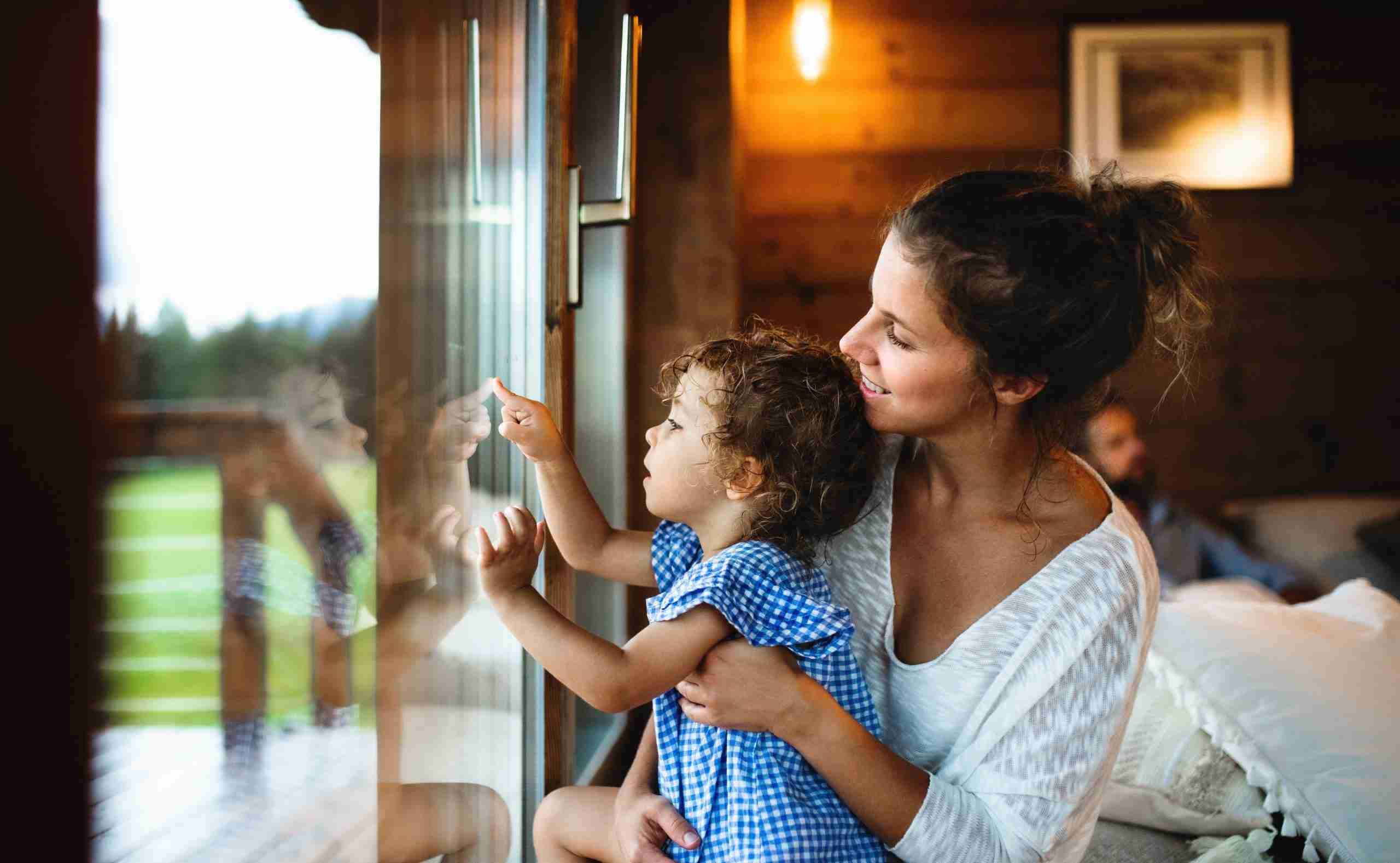 Mother and daughter looking out a window in a rental home