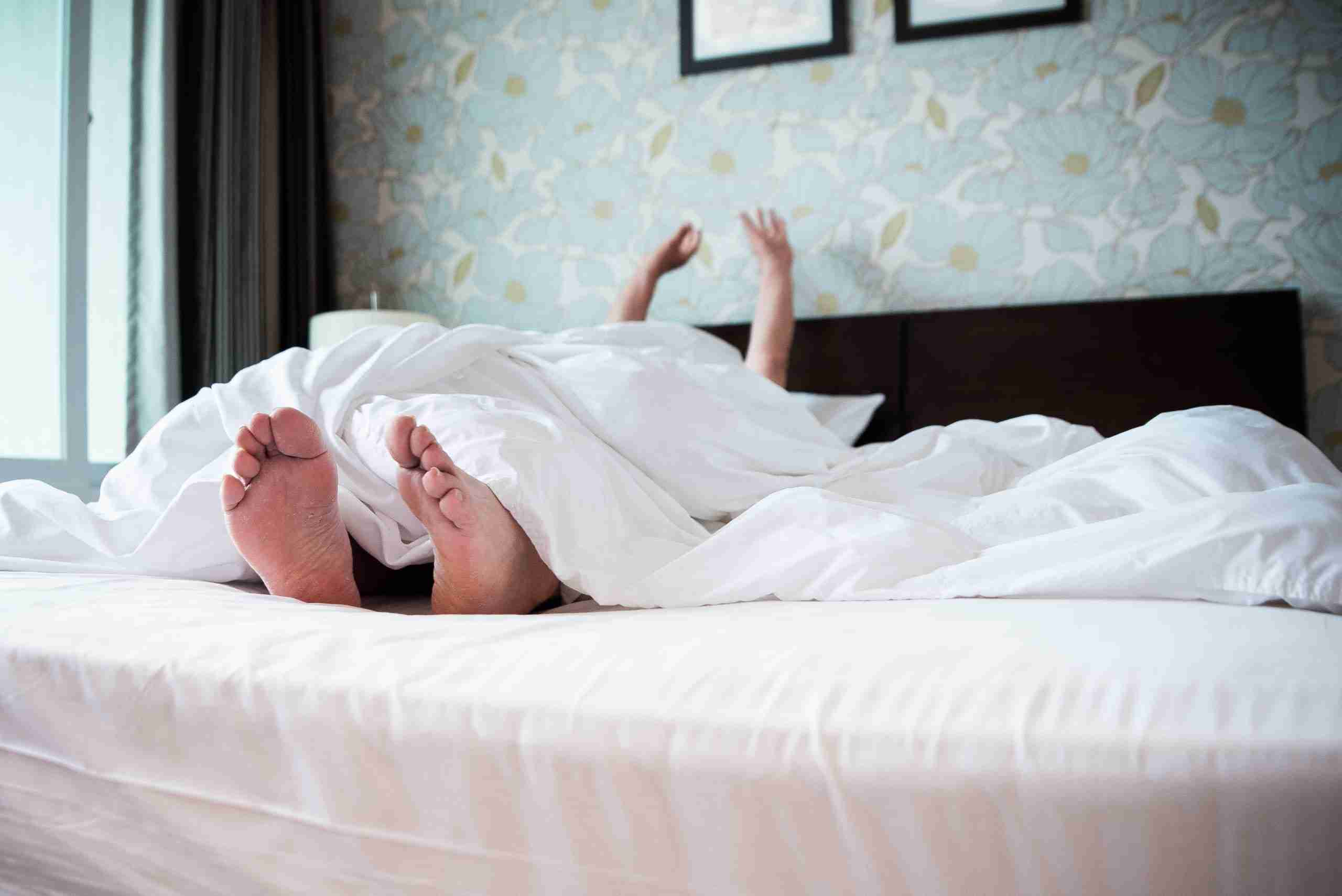 Person waking up in white bedsheets