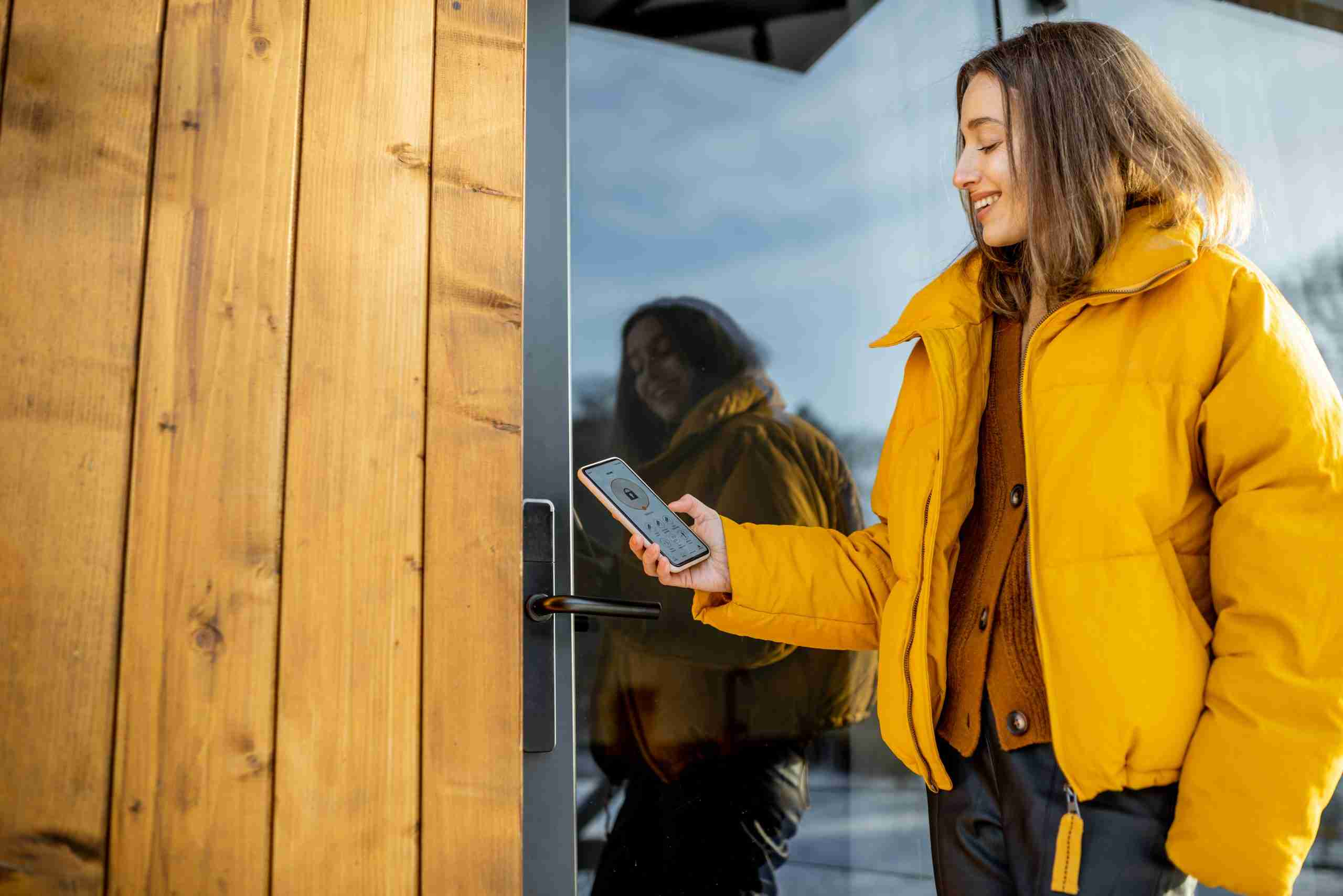 A woman manages her smart lock from her phone